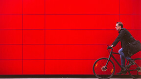 Man riding bicycle in front for red wall